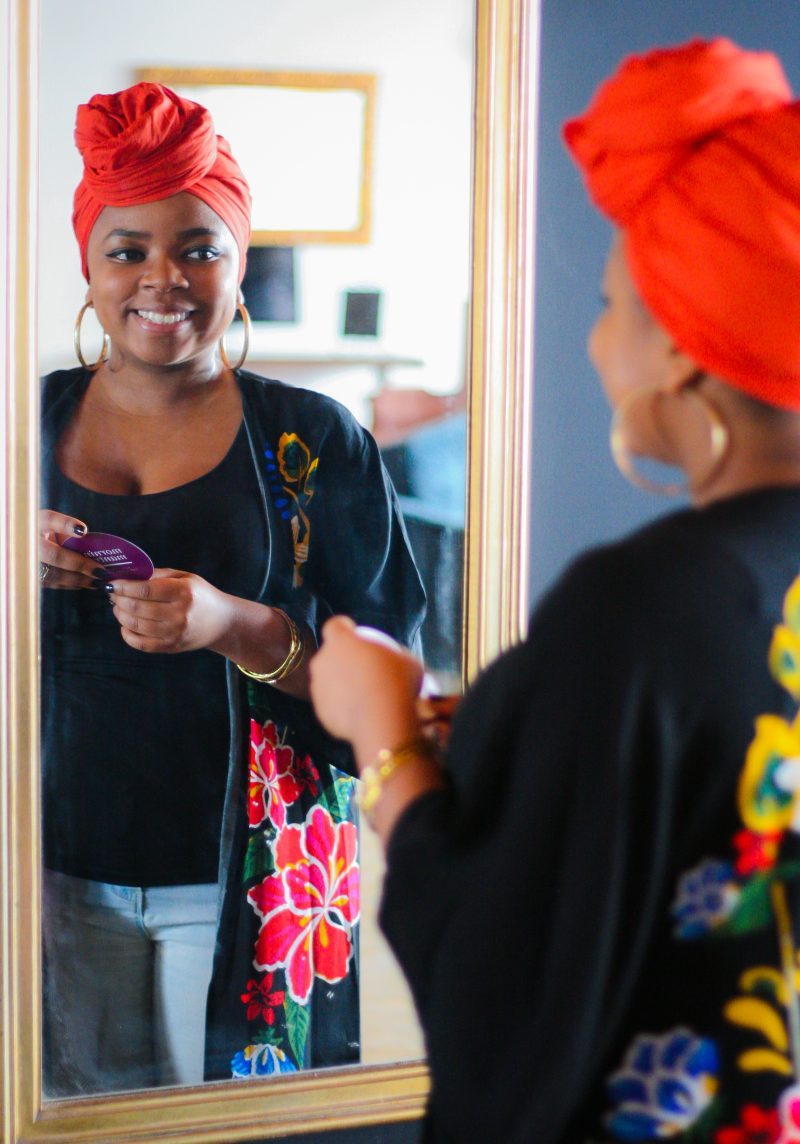 Tara Jefferson from The Renaissance Suite, LLC looking in the mirror at her self smiling as she reads an affirmation.