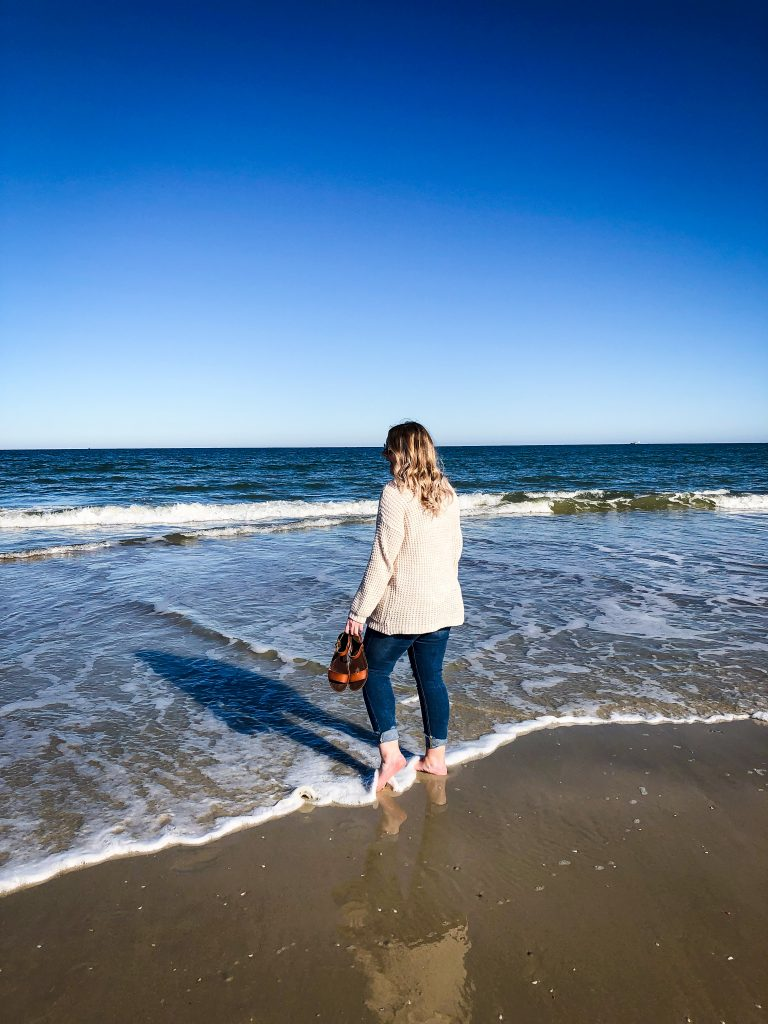 Girl walking on the beach with her feet in the water looking at the waves